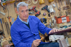 Portrait retired carpenter sitting at workshop Stock Photography