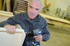 Portrait retired man working at workshop stock image