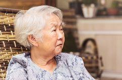 Portrait of a retired old woman seated with a concerned or sad e. Xpression. Japanese descendant, aligned to the left Royalty Free Stock Photo