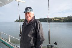 Portrait of a retired senior male tourist on a fishing charter b. Active retirement - portrait of a retired senior male tourist on a fishing charter boat at Royalty Free Stock Image