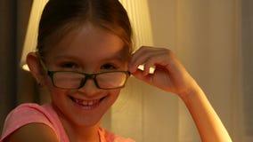 Portrait riant d'enfant de lunettes regardant la caméra, visage heureux 4K de sourire de fille banque de vidéos
