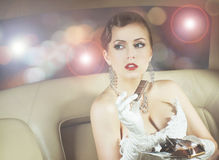 Portrait of a rich woman eating chocolate in a car Royalty Free Stock Photos