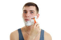 Portrait of a ridiculously young guy with foam on his face who shaves his beard machine Royalty Free Stock Image
