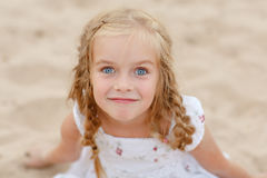 Portrait risible blonde girl with pigtails and blue round eyes.  Stock Photo