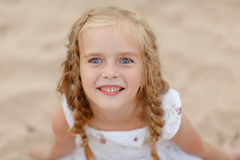 Portrait risible blonde girl with pigtails and blue round eyes.  Royalty Free Stock Images