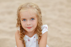 Portrait risible blonde girl with pigtails and blue round eyes.  Royalty Free Stock Photography
