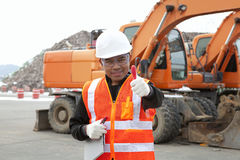 Portrait of road construction worker with heavy equipment. Portrait of driver construction equipment showing thumb up smiling Stock Image