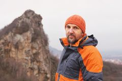 Portrait of a rock climber aged and with a beard against the backdrop of sharp mountain in the northern Caucasus Stock Photo