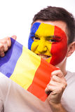Portrait of Romanian football fan of Romania national team with flag on grey background. Stock Photography