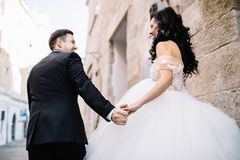 Portrait of a romantic beautiful couple traveler walking in the. Bride and groom walking through the old town Stock Photography