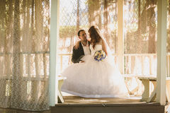 Portrait of romantic bride and groom sitting at alcove at sunny Royalty Free Stock Photography