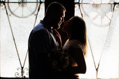 Portrait of a romantic couple in a backlight from a window or do. Or, silhouette of a couple in a doorway with a backlight, couple of lovers groom and bride at stock image