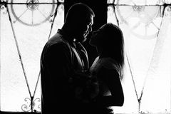 Portrait of a romantic couple in a backlight from a window or door, silhouette of a couple in a doorway with a backlight, couple o. F lovers groom and bride at Royalty Free Stock Image