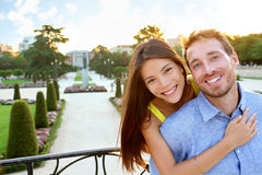 Portrait of Romantic couple embracing in love. Looking at camera. Multicultural men and women smiling happy in el Retiro in Madrid, Spain, Europe. Asian girl royalty free stock photography