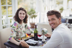 Portrait of romantic couple holding hands while having meal Royalty Free Stock Photography
