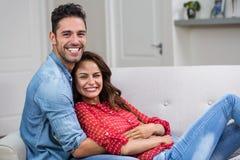 Portrait of romantic couple hugging on sofa Royalty Free Stock Photos
