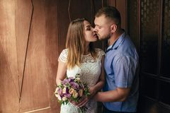 Portrait of a romantic couple,man and woman kissing in a dramati. Portrait of a romantic couple,man and women kissing in a dramatic light, girl holding flowers Royalty Free Stock Photos