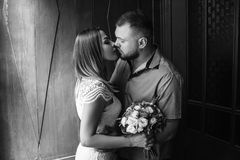 Portrait of a romantic couple,man and woman kissing in a dramatic light, girl holding flowers in hands, young beautiful bride in w. Portrait of a romantic couple Royalty Free Stock Photo