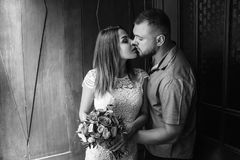 Portrait of a romantic couple,man and woman kissing in a dramatic light, girl holding flowers in hands, young beautiful bride in w. Portrait of a romantic couple Stock Photography