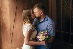 Portrait of a romantic couple,man and woman kissing in a dramatic light, girl holding flowers in hands, young beautiful bride in w stock image