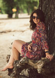 Portrait of romantic girl in dress sitting under tree Royalty Free Stock Images