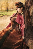 Portrait of romantic girl in historical dress. Beautiful romantic woman in historical dress sits in the autumn on the nature stock images