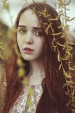 Portrait of a romantic girl with red hair in the wind under a willow tree. Portrait of a romantic girl with red long hair in the wind under a willow tree stock images