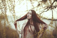 Portrait of a romantic girl with red hair in the wind under a willow tree.