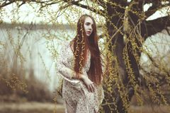 Portrait of a romantic girl with red hair in the wind under a willow tree. Portrait of a romantic girl with red long hair in the wind under a willow tree royalty free stock photos