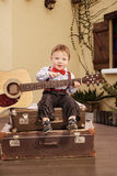 Portrait of a romantic little boy sitting with guitar. Portrait of a romantic little boy sitting with his guitar. Retro style Stock Photos