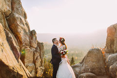 Portrait of romantic newlywed couple going to kiss in sunset lights on majestic mountain landscape with big rocks as. Backround stock image