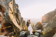 Portrait of romantic newlywed couple holding each other in sunset lights on majestic mountain landscape with big rocks. As backround royalty free stock photos