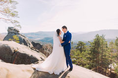 Portrait of romantic newlywed couple in sunlight on rocky cliff with mountain landscape as backround Royalty Free Stock Images