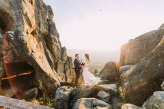 Portrait of romantic newlywed couple in sunset lights on majestic mountain landscape with big rocks as backround Royalty Free Stock Photo
