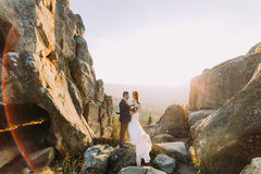 Portrait of romantic newlywed couple in sunset lights on majestic mountain landscape with rocky cliffs as backround Stock Photos