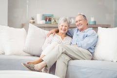 Portrait of romantic senior couple sitting on sofa in living room Stock Photography