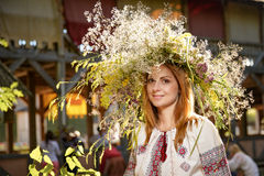 Portrait of a romantic smiling woman in a circlet of flowers. Outdoors Stock Photos