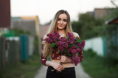 Portrait of a romantic smiling young woman with a bouquet of lilac outdoors shallow depth of field Royalty Free Stock Photography