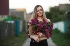 Portrait of a romantic smiling young woman with a bouquet of lilac outdoors shallow depth of field Stock Image