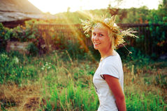 Portrait of a romantic smiling young woman in a circlet of flowers outdoors. Evening sun shining Royalty Free Stock Photography