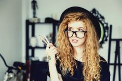 Feemale Tattoed Artist With Pencil. Portrait of romantic tattoed curly painter girl in a black hat wears eyeglasses hold pencil stock image