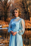Portrait of romantic woman in a dress on the bank of the river Royalty Free Stock Images