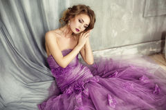 Portrait of the romantic woman in a lilac dress. Romantic woman in a purple dress sitting against the wall Royalty Free Stock Image