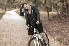 Handsome caucasian man with round eyeglass and earphones bicycling in the park stock images