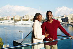 Portrait of romantic young couple enjoying view at Barcelona. Men and women standing on the balcony with beautiful yacht port background during their spring Royalty Free Stock Images