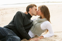 Portrait Of Romantic Young Couple Kissing On Beach Stock Images