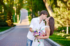 Portrait of romantic young couple kissing on the road in summer day Stock Photos