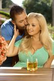 Portrait of romantic young couple kissing. At summer garden, outdoors. Attractive, busty blonde women with cleavage Royalty Free Stock Photo
