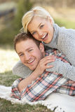 Portrait Of Romantic Young Couple Lying On Grass Royalty Free Stock Image