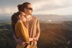 Portrait of a romantic young hipster couple hugging. They stand in an embrace in nature high in the mountains against. The backdrop of a mountain green valley royalty free stock photos